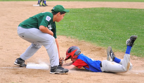 Old Town's Cree Neptune Bear (left) tags out Bangor West's Ethan Scripture at third base during their District 3 Little League all-star game in Bangor Monday afternoon.