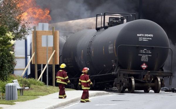 Firefighters walk past a burning train wagon after an explosion at Lac-Megantic, Quebec, on Saturday.