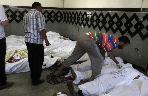 Men search for the bodies of relatives among the deceased supporters of deposed Egyptian President Mohammed Morsi at a field hospital near the scene of clashes between pro-Morsi supporters and police in Nasr city area, east of Cairo on July 27, 2013.