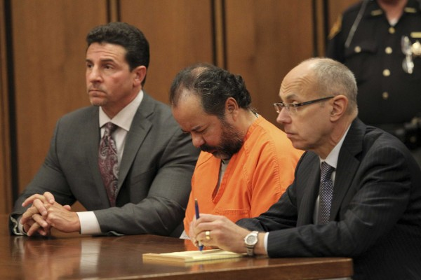Ariel Castro sits with his head down between his attorneys Jaye Schlachet (R) and Craig Weintraub (L) during his pre-trial hearing on charges including rape, kidnapping and murder in Cleveland, Ohio in this file photo taken June 19, 2013.  Castro was found competent to stand trial on July 3, 2013.
