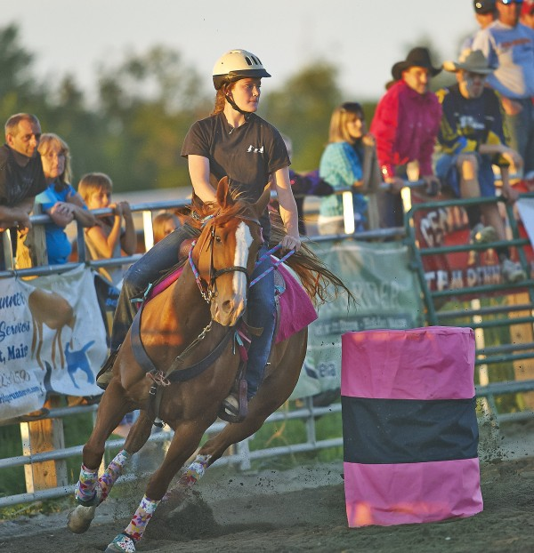 Paige Garcia, riding Red Fury, competes in the Barrel Racing event at the rodeo Saturday night at the Maple Lane Farm in Charleston.  BDN photo by Michael York