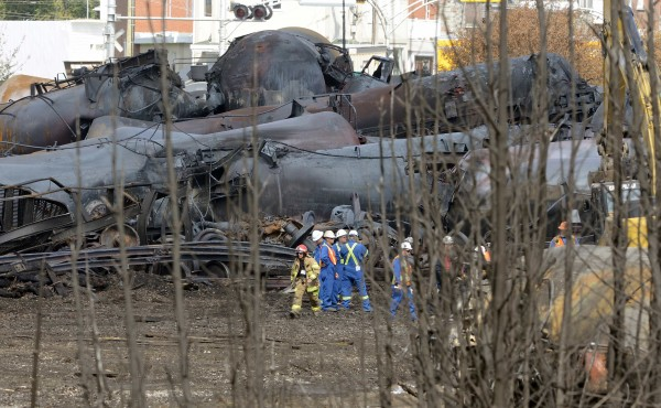 A firefighter and an emergency crew work on the site of the train wreck in Lac Megantic, July 16, 2013. The crude oil freight train that derailed and blew up in the small town of Lac-Megantic early on Saturday morning was traveling far too fast when it went off the rails, investigators told reporters on Tuesday.
