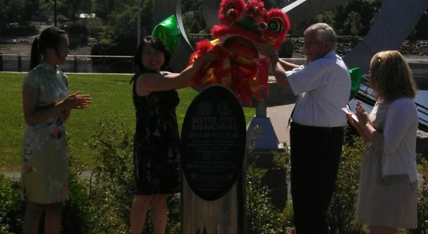 Jing Zhang, president of the Bangor Chinese School, and Bangor City Council Chairman Nelson Durgin, unveil a monument recognizing the sister-city relationship between Bangor and Harbin, China on Monday, July 15, at the Bangor Waterfront.