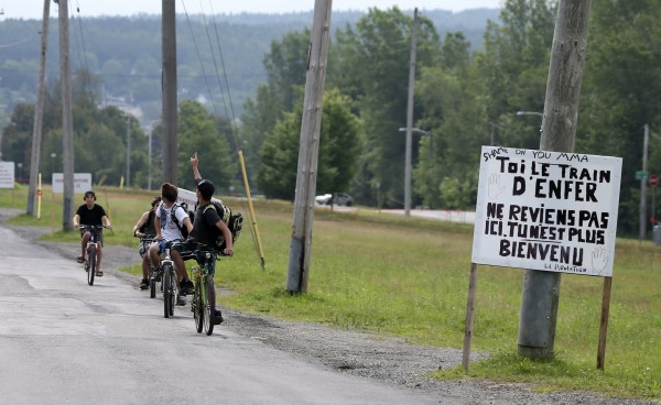 A group of boys cycles toward a sign posted beside train tracks reading, &quotYou, the train from Hell, do not come here anymore, you are not welcome. Signed the population&quot in the town of Lac-Megantic, Quebec July 11, 2013. Residents of the town of Lac-Megantic in Quebec were coming to grips on Thursday with the reality that 50 of their own were most likely dead in the aftermath of the worst railway disaster in North American in more than two decades.