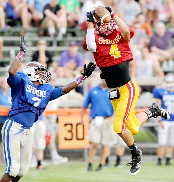 East wide receiver Matt Cosgrove of Bangor High School hauls in a second-quarter pass against West defensive back Damien Shepard of Windham High School during the Maine Shrine Lobster Bowl Classic in Biddeford on Saturday.