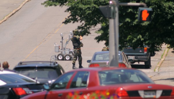 A Bangor Police Special Response Team member aims a gun at the window of a Park Street apartment, where man fired 70 or more rounds from a gun on Thursday.
