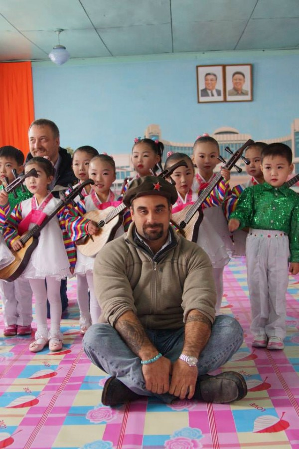 Joseph Ferris, a Maine Maritime Academy graduate and native of China, Maine, who now leads tours to North Korea, poses with a classroom of children on one of his recent trips there.