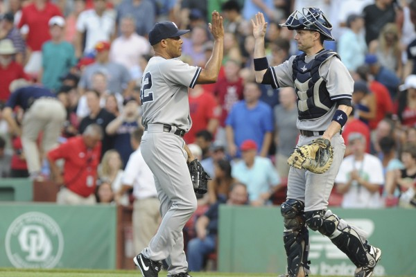 New York Yankees relief pitcher Mariano Rivera (42) high fives catcher Chris Stewart (19) after defeating the Boston Red Sox at Fenway Park in Boston Saturday.