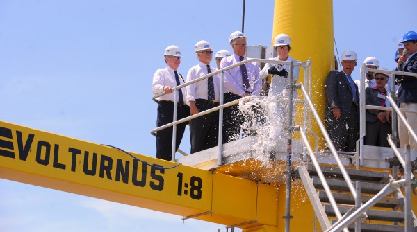 Sen. Susan Collins breaks a bottle of champagne on the VolturnUS 1:8 unit before it is lifted into the Penobscot River at the Cianbro Corporation Brewer facility Friday.  The VolturnUS 1:8 is the first offshore wind turbine that launched in North America will be towed down the Penobscot River as the weather allows and it will be moored in the East channel of the Penobscot Bay near Castine.