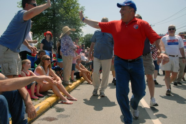 Gov. Paul LePage high-fives a bystander as he walks in Brewer during a Fourth of July parade on Thursday.