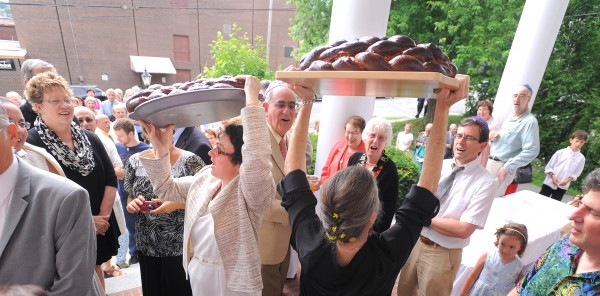 Rabbi Darah Lerner (left) and her spouse Kelly Quagliotti hold up loaves of challah as they say a blessing of food before their wedding reception at Congregation Beth El in Bangor on Sunday afternoon.