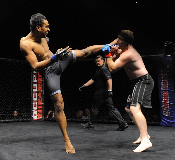 Damon Owens of Bangor (left) kicks John Raio, sending him to the mat and ending the fight in 35 seconds during a mixed martial arts bout on the Bangor waterfront Friday night, July 12, 2013.