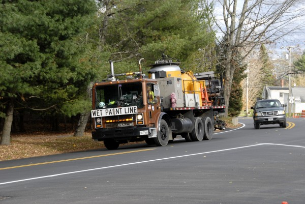 A Maine Department of Transportation truck and driver paint a white line along the west-bound edge of Route 2 in downtown Carmel in October 2012.