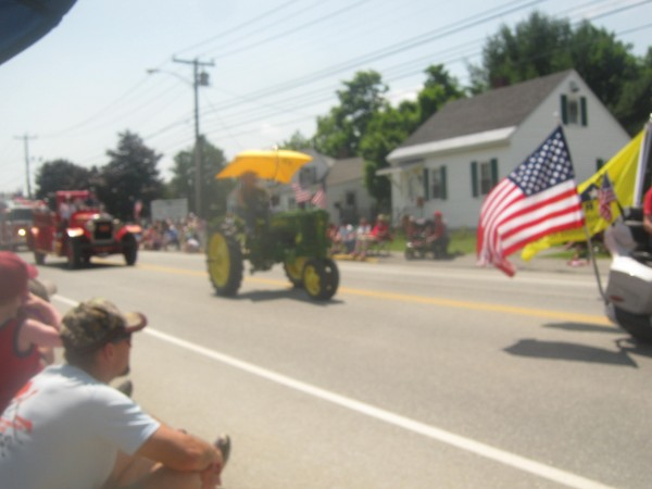 The antique tractor rides along in the Fourth of July parade on Wilson Street in Brewer. An accident involving the vehicle and an antique firetruck later occurred on Water Street where the man on the tractor was killed.