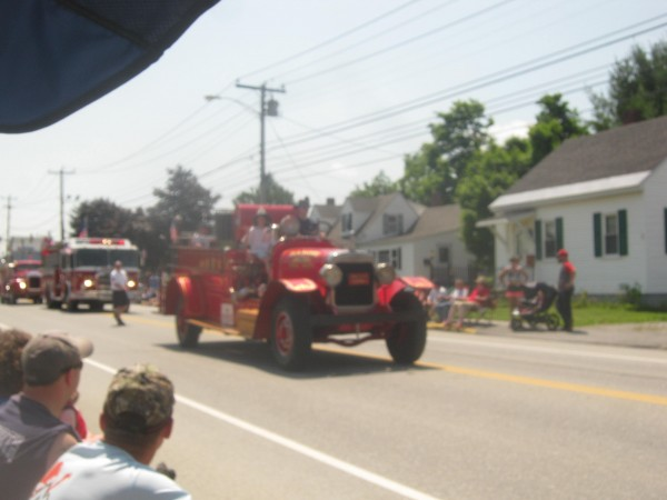 The antique firetruck rides along behind the antique tractor in the Fourth of July parade on Wilson Street in Brewer. An accident involving the vehicles later occurred on Water Street where the man on the tractor was killed.