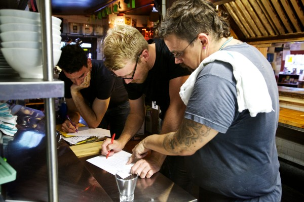 Chef Rocco Salvatore Talarico of Supperpie (right) goes over the night's menu with servers David Timm (center) and Chris Stiegler at a South Portland pop-up, nine-course dinner.