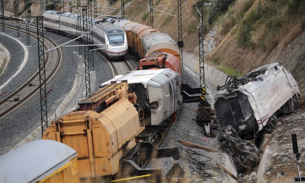 A passenger train drives past the site of a train crash, with the train engine derailed from the track, in Santiago de Compostela, northwestern Spain on Saturday.