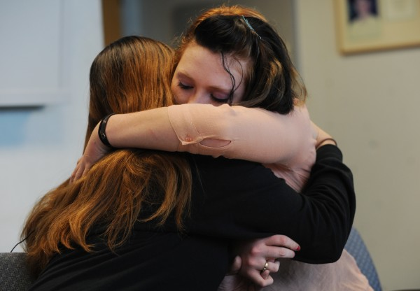 Angie Ouellette, mother of Christopher Killian, 14, of Corinth who was found unconscious and bloodied on Route 15 late Friday night, hugs her daughter Ashley after asking the media for help in finding out what happened to her son during a press conference at Eastern Maine Medical Center in Bangor on Tuesday.