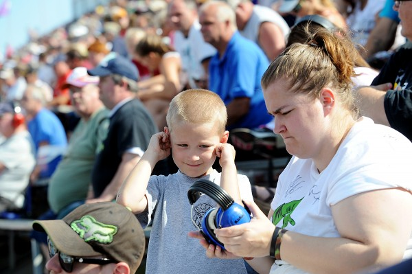 Adam Young, 6, of Bangor protects his ears from the noise of race cars at Oxford Plains Speedway on Sunday while his mother, Sasha Rolland, fixes his ear protection.