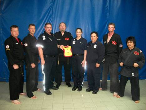 David Stewart of Caribou suffered cardiac arrest during a karate class he was taking in April, and instructors from the class, along with The Aroostook Medical Center's Crown Ambulance and Critical Care Transport team are credited with saving his life. Posing with the automated external defibrillator that was used to help save Stewart's life are Sensei Mitch Wheeler, Sensei Jay Peavey, TAMC Flight Nurse Darrell Spooner, Head Sensei Bill Graves, TAMC Flight Medic Kim Whitaker, TAMC Paramedic Kenna Prue, Sensei Jerod Kingsbury, and Sensei Lucy Newbegin.