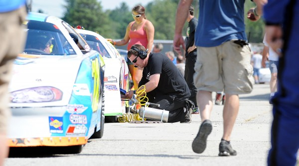 Jamie Schureman of Glenburn, a tire specialist for the 70 car driven by Trevor Sanborn, adds air to the tires before their qualifying heat Sunday at Oxford Plains Speedway. Sanborn advanced to the feature TD 250 race.