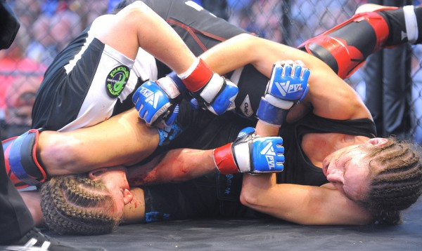 Tara Mitchell (right) and Kim Russell fight in the 135-pound class during their MMA match at the Bangor Waterfront.  Mitchell won the fight.