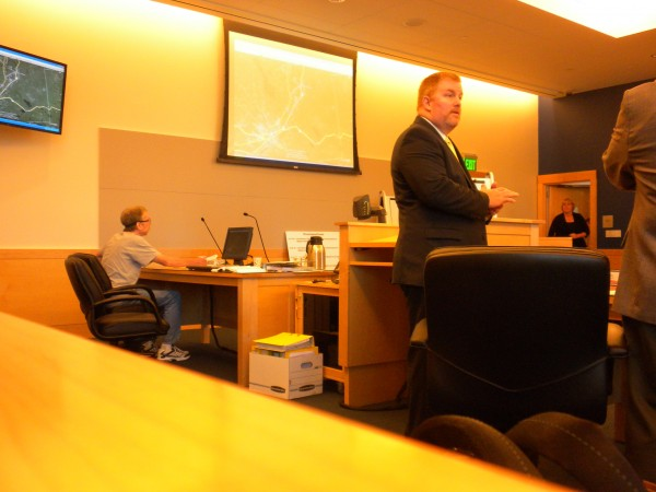 John A. Weckerly, who is charged with 12 crimes, including four arsons, sits at the defense table at the Penobscot Judicial Center on July 25, 2013 while his attoreny, Kirk Bloomer, discusses an item with Penobscot County District Attorney R. Christopher Almy, on right.