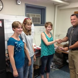 Brunswick Police Lt. Michael Moody, right, presents Rose Edwards, Sophie Smith and Julianna Nelson with $800 cash, which they found and turned into police more than 13 months ago.