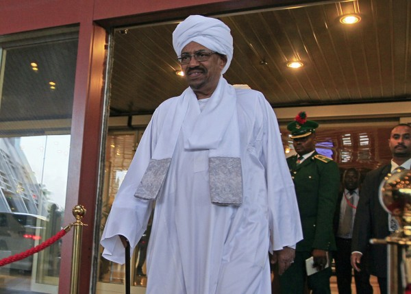 Sudanese President Omar al-Bashir walks out of a hotel in Abuja July 14, 2013. Al-Bashir arrived in Nigeria on Sunday for an African Union summit on HIV/AIDS as his hosts chose to ignore an International Criminal Court (ICC) arrest warrant against him.