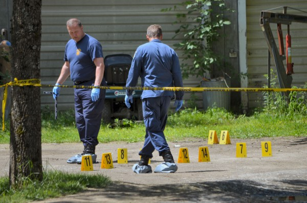 State police evidence team members mark off evidence outside of 24 Main St. in Detroit late Thursday morning.