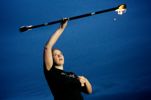 Brigid Sinclair Rankowski of Dark Follies spins a fire staff above her head on Portland's East End Beach Friday night. Dark Follies recently had a hand in writing new city rules regarding fire performing.