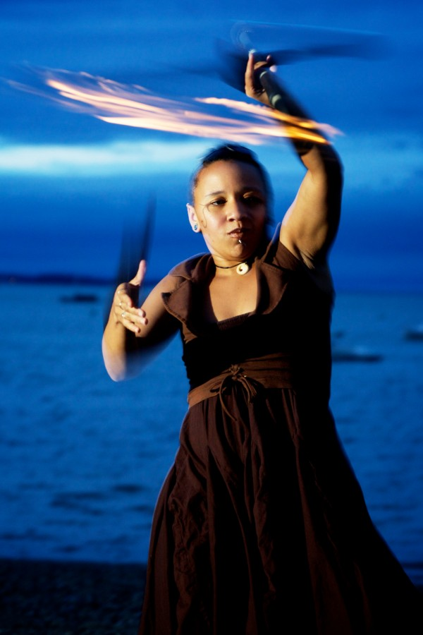 Rosa Libby of Dark Follies spins a fire staff above her head on Portland's East End Beach Friday night. Dark Follies recently had a hand in writing new city rules regarding fire performing.