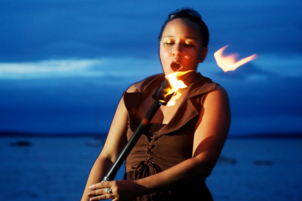 Rosa Libby of Dark Follies blows out her fire staff on Portland's East End Beach Friday night. Dark Follies recently had a hand in writing new city rules regarding fire performing.