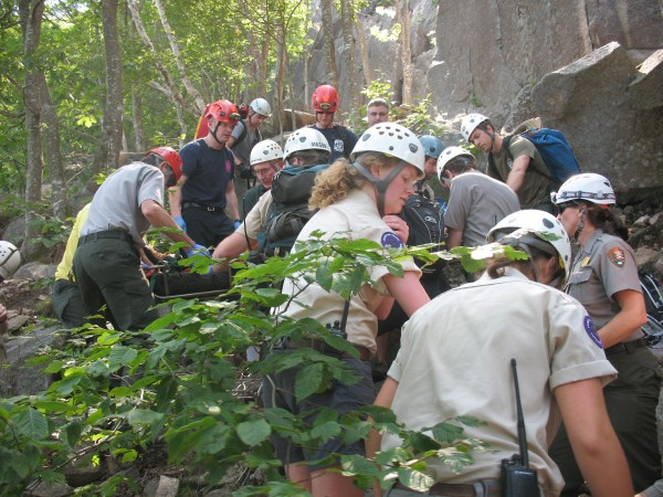 Acadia National Park rangers and other responders carry a climbing guide in a litter to the bottom of Champlain Mountain on Wednesday, July 17, 2013, after he fell 40 feet on the South Wall section of the mountain. Rangers said he suffered &quotmulti-trauma&quot injuries in the fall.