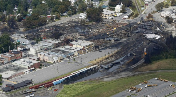 A aerial view of the wreckage of the crude oil train is seen in Lac Megantic, July 8, 2013. A driverless, runaway fuel train that exploded in a deadly ball of flames in the center of a small Quebec town started rumbling down an empty track just minutes after a fire crew had extinguished a blaze in one of its parked locomotives, an eyewitness said on Monday.