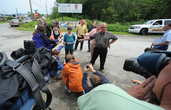 Members of the media surround activist Nancy Galland of Stockton Springs as she reads a statement about the recent oil train derailment in Lac-Megantic, Quebec, while standing at the entrance to Montreal, Maine & Atlantic Railroad in Hermon on Monday.