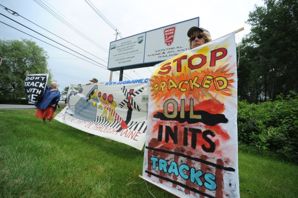Activists with 350 Maine hold signs and banners to draw attention to the recent oil train derailment in Lac-Megantic, Quebec, while standing at the entrance to Montreal, Maine and Atlantic Railroad in Hermon on Monday.