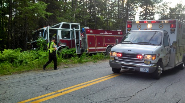 A Penobscot County Sheriff's deputy surveys the damage to a Carmel Fire Department rescue pumper that veered off Route 69 on the evening of July 7, 2013, on its way to a call.