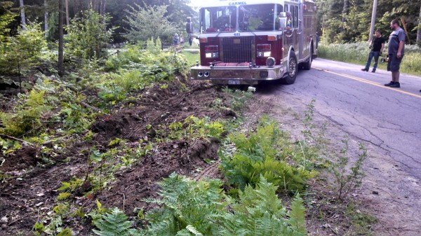 A Carmel Fire Department rescue pumper is pulled from a ditch by a large tow truck. The firetruck veered off Route 69 in Carmel on the evening of July 7, 2013, on its way to a call.