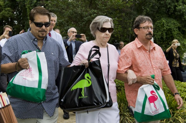 Gloria C. Mackenzie, an 84-year-old woman from Zephyrhills, Florida (center), her son Scott (right) and a person identified by Lottery Officials as &quota trusted family friend&quot (left) leave the Florida Lottery offices after claiming the largest single Powerball jackpot in American lottery history, valued at $590 million, in Tallahassee, June 5, 2013.