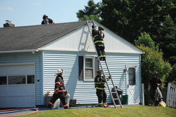 Firefighters from Brewer and Bangor work to extinguish a house fire at 77 Birchwood Blvd. in Brewer on Monday. Two adults and two children escaped without injury.