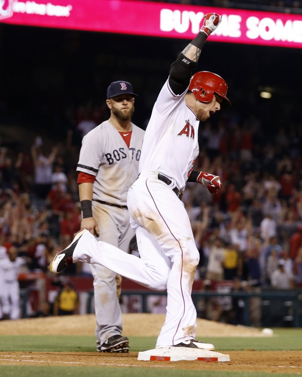 Los Angeles Angels' Josh Hamilton rounds first base while celebrating his game winning walk-off two-run home run as Red Sox first baseman Mike Napoli looks on during the 11th inning in Anaheim, Calif., July 6, 2013.