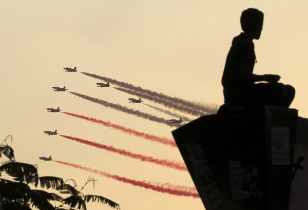 A man is silhouetted against the sunset as Egyptian military jets fly in formation over Tahrir square in Cairo on Thursday, July 4, 2013. The leader of the Muslim Brotherhood was arrested by Egyptian security forces on Thursday in a crackdown against the Islamist movement after the army ousted the country's first democratically elected president Mohamed Morsi.