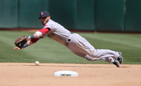 Boston Red Sox second baseman Dustin Pedroia (15) makes a diving catch on a ground ball hit by Oakland's Coco Crisp in the seventh inning Sunday at O.co Coliseum. Crisp beat Pedroia's throw to second, ending a no-hit bid by Red Sox rookie right-hander Brandon Workman.