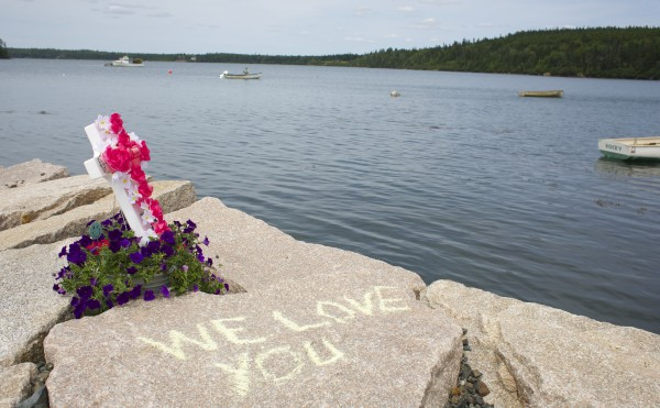 Family members of Melissa Moyer place memorials and draw chalk writings in memory of Moyer and Amy Stiner who died after apparently becoming disoriented in the fog and driving off a boat ramp on Schoppee Point Road in Roque Bluffs Tuesday night.