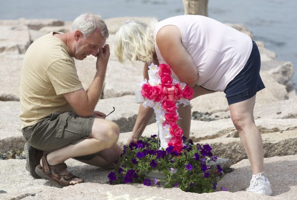 David Moyer and Debbie Moyer, parents Melissa Moyer place memorials and draw chalk writings in memory of Moyer and Amy Stiner who died after apparently becoming disoriented in the fog and driving off a boat ramp on Schoppee Point Road in Roque Bluffs Tuesday night.