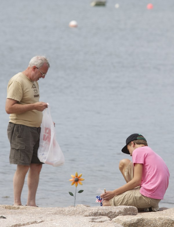 David Moyer and Alex Reichner, 13,  family members of Melissa Moyer place memorials and draw chalk writings in memory of Moyer and Amy Stiner who died after apparently becoming disoriented in the fog and driving off a boat ramp on Schoppee Point Road in Roque Bluffs Tuesday night.