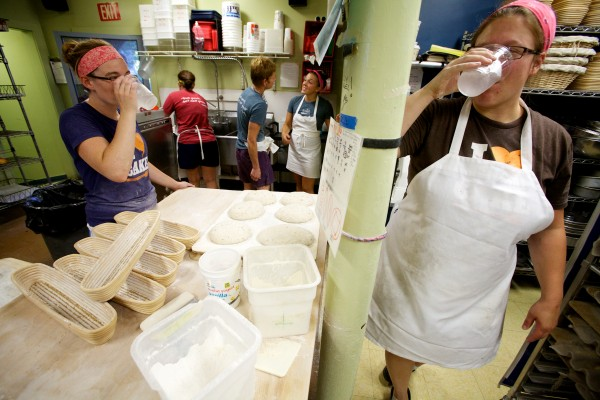 Melanie Roy (left) and Emily Pappas down some ice water while making bread at Scratch Baking Co. in South Portland Wednesday morning. Temperatures can top out at over a hundred degrees on a hot day in front of the ovens.