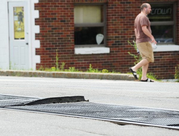 A pedestrian crosses State Street near the rail road tracks in Brewer on Tuesday. Brewer officials are concerned that the rubber mat between the rails has become dislodged.