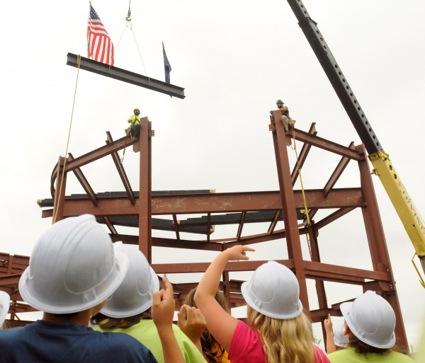 Children watch as a steel beam is lifted into place during the topping-off ceremony for the new Emera Astronomy Center at the University of Maine in Orono Monday.